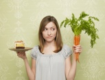 Woman choosing between cake and carrots